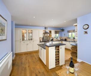 photo of beige blue orange white dining area kitchen with flooring island kitchen mixer taps spotlights wooden floor and extractor hood furniture glazed cabinet wine rack