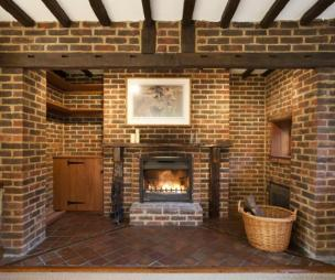 photo of beige brown orange brickwork lounge with brick fireplace feature fireplace fireplace inglenook fireplace low ceilings wooden beams