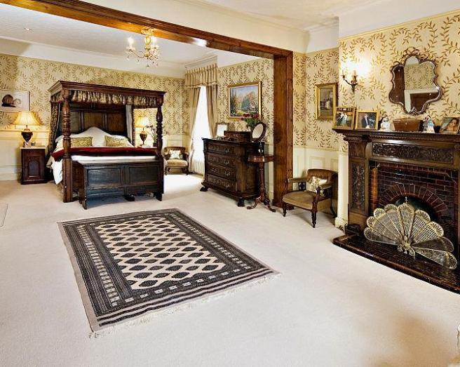 photo of antique beige brown white bedroom with wall lights fireplace carpet rug rugs wallpaper and furniture wooden cupboard