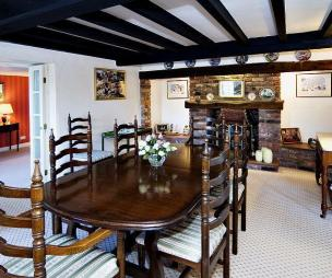photo of classic blue brown white dark wood dining room with inglenook fireplace upholstery
