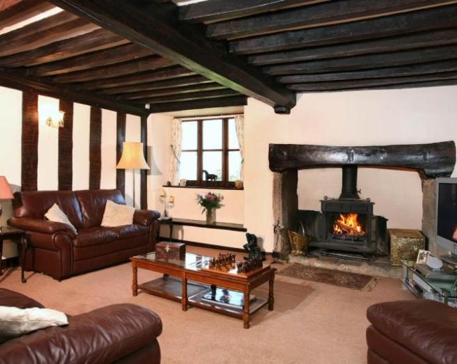 photo of beige brown living room lounge with exposed beams fireplace inglenook wood burner and furniture leather sofa sofa