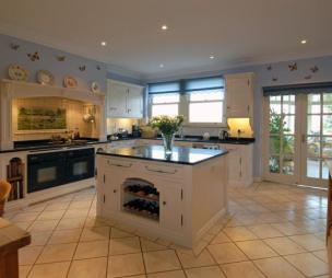 photo of beige blue brown kitchen with breakfast bar blue blind decorative plates and range cooker furniture wine rack