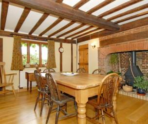photo of brown oak dining room with beams fireplace inglenook fireplace wood burner
