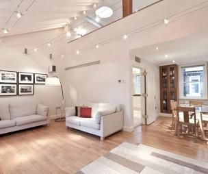 photo of open plan beige white living room reception with lighting track wooden floor