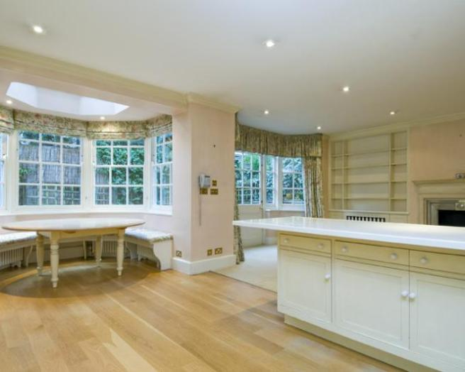photo of beige white kitchen with bay window and furniture oval table