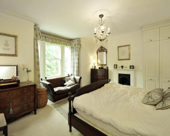 photo of traditional updated traditional victorian style cream bedroom master bedroom with chandelier fitted wardrobes mirror bay window fireplace high ceilings and couch in bay