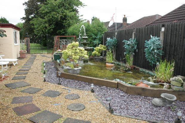 landscaped garden with ornamental pool and water feature