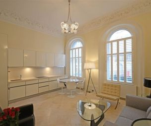 photo of classical open plan cream living room with white kitchen cabinets cornice