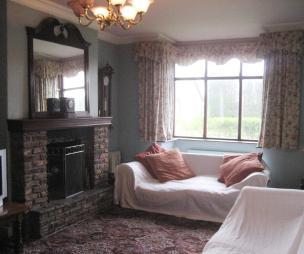 photo of black pink white lounge with brick fireplace fireplace