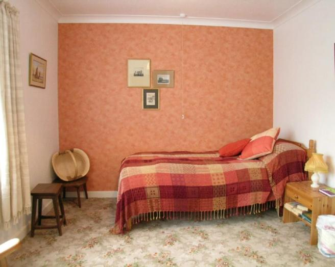 photo of beige orange peach bedroom with carpet tartan wallpaper