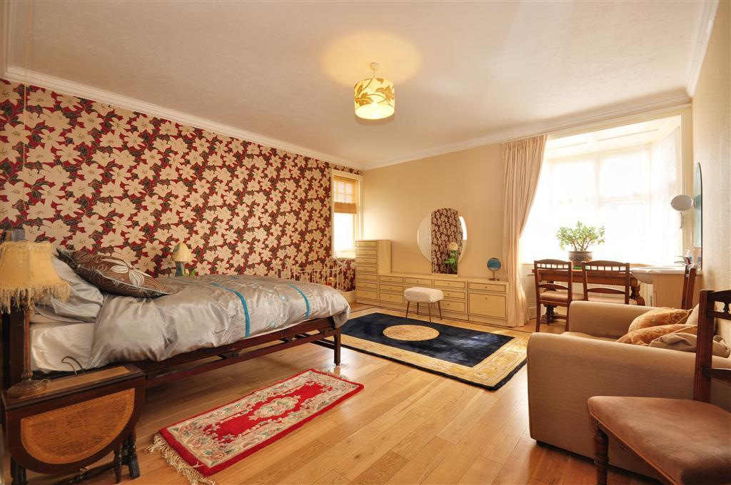 photo of beige brown orange bedroom with feature wall rugs soft furnishings wallpaper and half moon table