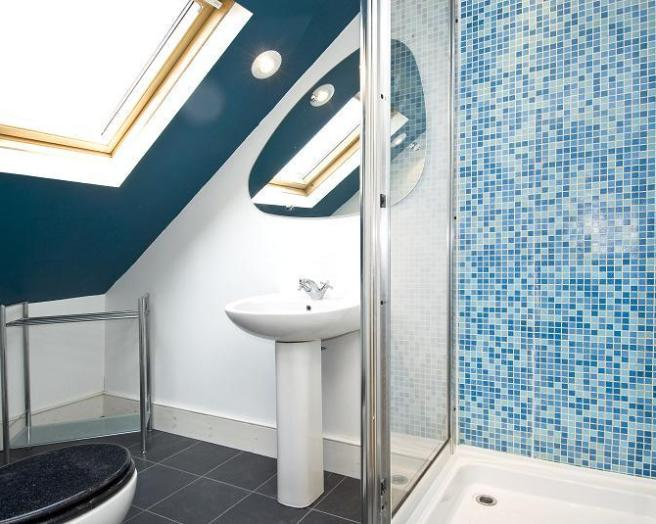 photo of colourful blue white bathroom loft conversion with floor tiles flooring shower tiled floor tiles en suite mosaic tiling spotlight