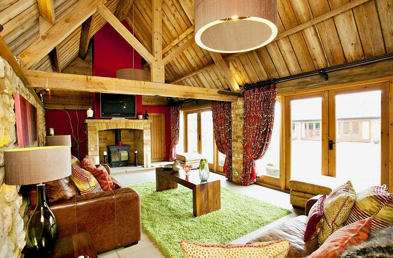 photo of barn conversion comfy green furry timber family room living room lounge with lighting wood burner and coffee table