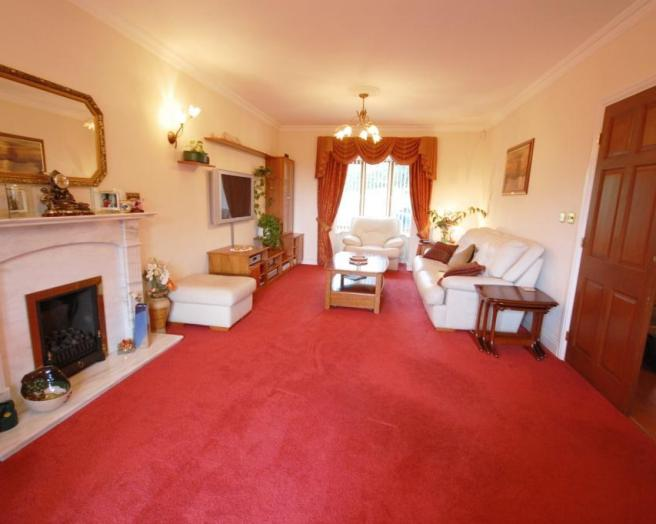 photo of traditional beige pink red white living room lounge with carpet and nested tables