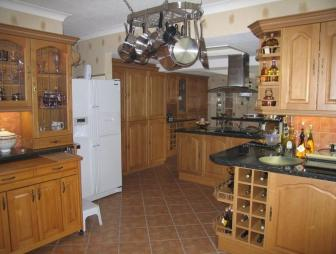 photo of beige brown orange white kitchen with floor tiles flooring tiled floor and extractor hood furniture glazed cabinets wine rack
