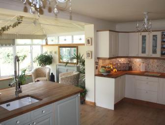 photo of beige brown white wood trim extension kitchen kitchen extension with chandelier white kitchen cabinets wooden worktop hardwood floor wooden floor