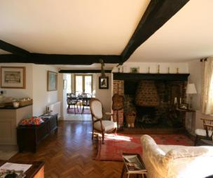photo of rustic lounge with exposed beams inglenook fireplace open fire parquet flooring