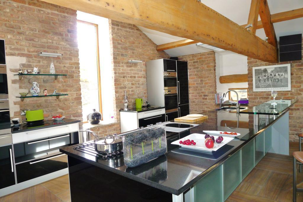 photo of contemporary luxury open plan beige black orange white exposed bricks kitchen with beams original features