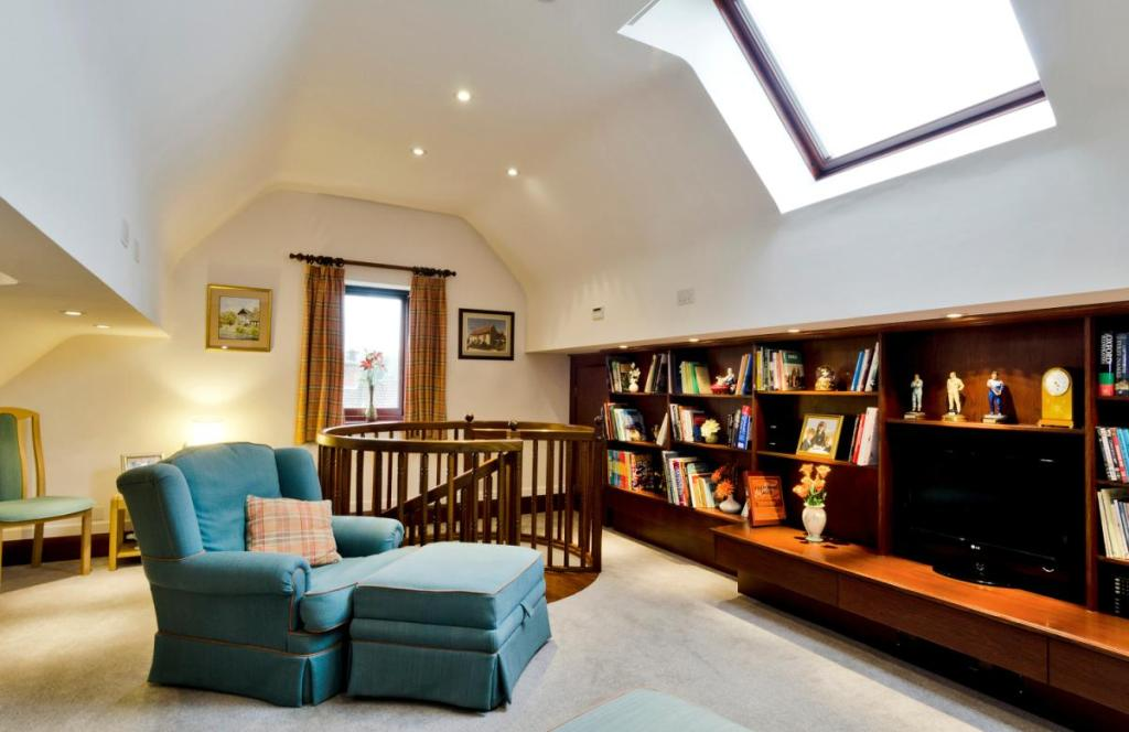 photo of beige white loft conversion reading room with spiral staircase staircase stairs and built-in bookcase