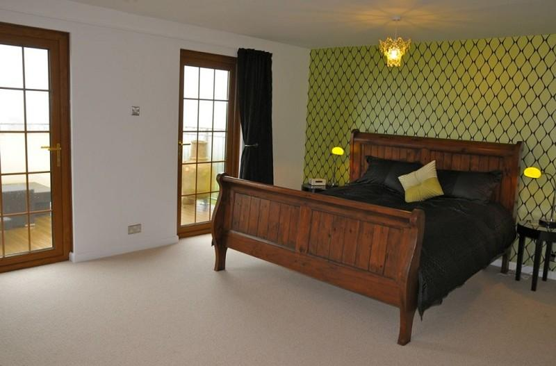 photo of beige brown green olive bedroom master bedroom with wooden floor feature wall wallpaper