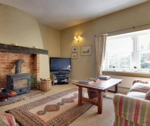 photo of beige brown white living room with wood burner