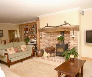 photo of beige white lounge with brick fireplace fireplace fireplace - wood burning stove fireplace surround open fireplace wood burner