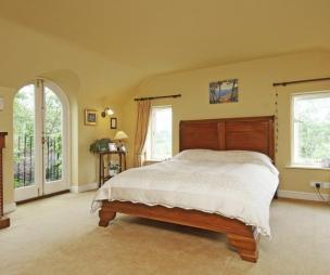 photo of large light beige orange yellow bedroom master bedroom with juliet balcony carpet carpeted