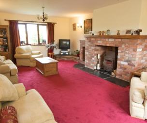 photo of beige cerise red drawing room lounge with brick fireplace