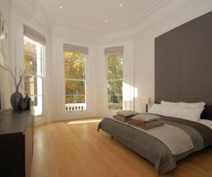 photo of contemporary modern brown cream white bedroom with bay window high ceilings original features sash windows and furniture headboard large headboard