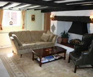 photo of beige black white drawing room lounge with exposed beams fireplace inglenook fireplace and armchair furniture