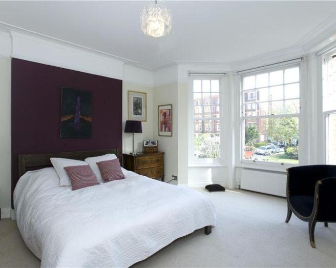 photo of blue purple white bedroom with bay window high ceiling cushions feature wall soft furnishings