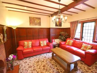 photo of beige brown orange red living room lounge with chandelier carpet floral carpet patterned carpet and furniture red sofa sofa