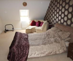 photo of comfy brown metallic bedroom with gabled ceiling feature wall pattern wallpaper and low furniture