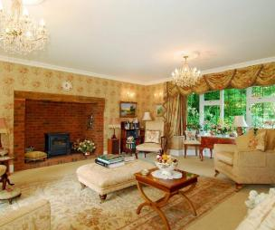photo of beige orange with brick fireplace fireplace wood burner chandeliers rug rugs and foot stool furniture
