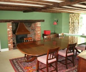 photo of green pink dining room with bay window exposed beams inglenook wood burner gingham rug rugs