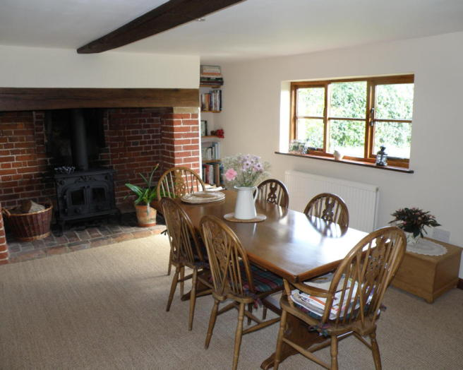 photo of beige brown white dining room with brick fireplace fireplace wicker basket and cast iron stove stove