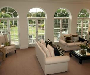 photo of beige black black&white cream white living room lounge sitting room with doors to garden arched window windows carpet and coffee table furniture