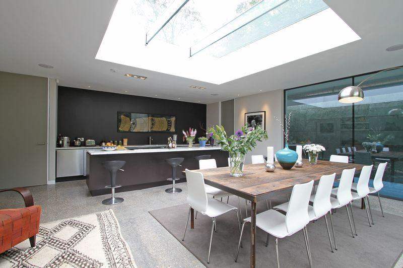 photo of contemporary white dining room kitchen with skylight