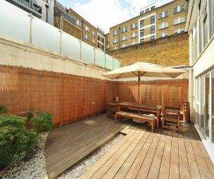 photo of low maintenance gravel garden with wood floor and decking urban garden