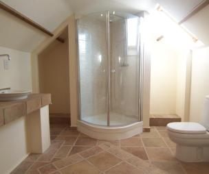 photo of practical beige brown white attic conversion bathroom loft conversion with floor tiles flooring shower shower cubicle terracotta tiles tiled floor skylight wooden beams