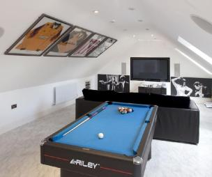 photo of blue white den games room home cinema loft conversion loft room with gabled ceiling signed football kits and furniture pool table