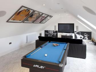 photo of blue white den games room home cinema loft conversion loft room mancave with gabled ceiling signed football kits and furniture pool table