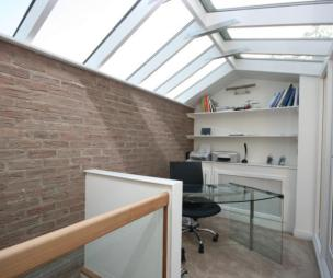 photo of minimalist natural light white exposed brick study with glass roof skylight