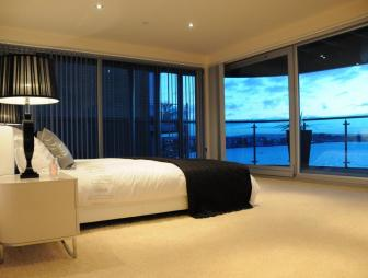 photo of contemporary modern spacious beige black blue balcony bedroom with glass wall blinds carpet and terrace