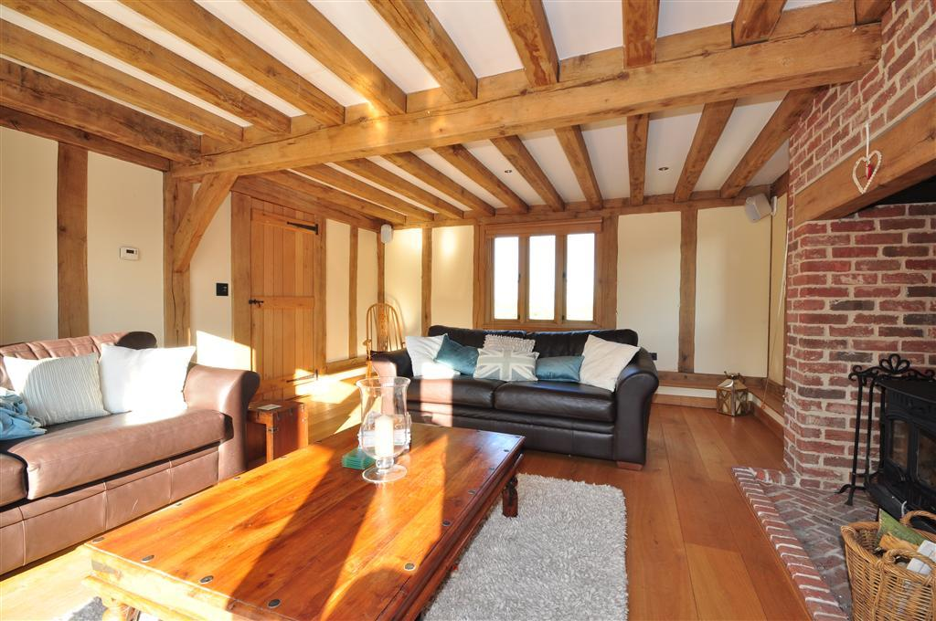 photo of beige timber woody lounge sitting room with brick fireplace exposed beams