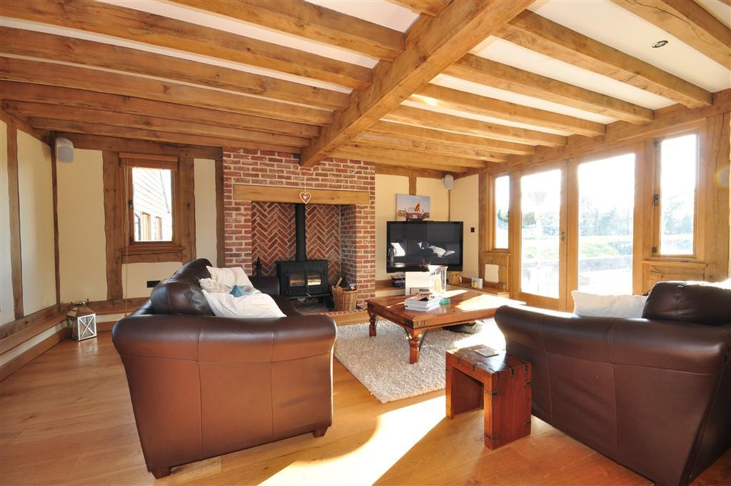 photo of geometric living room lounge sitting room with brick fireplace fireplace oak beams and furniture leather sofa sofa