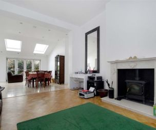photo of green white living room with fireplace parquet flooring wood burner rug