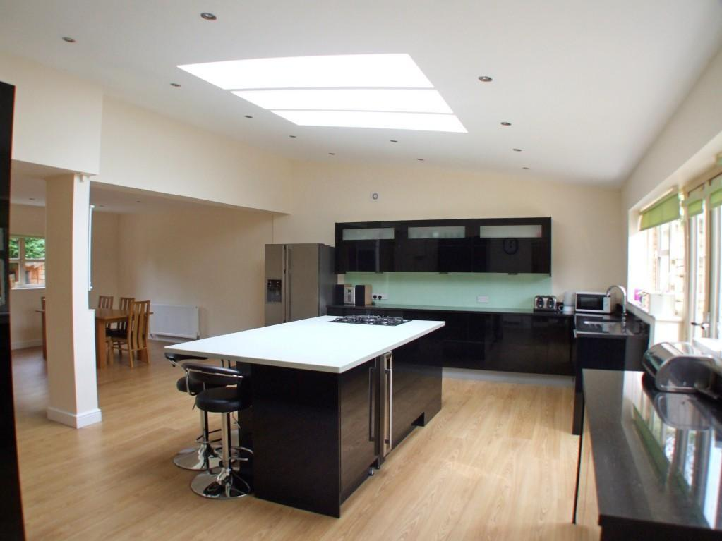 photo of contemporary luxury open plan beige black white kitchen kitchen extension with breakfast bar