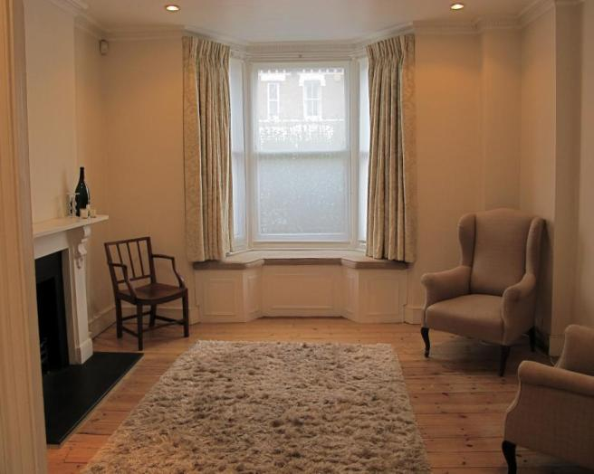 photo of beige brown with bay window window seat furry rug and armchairs bench seat