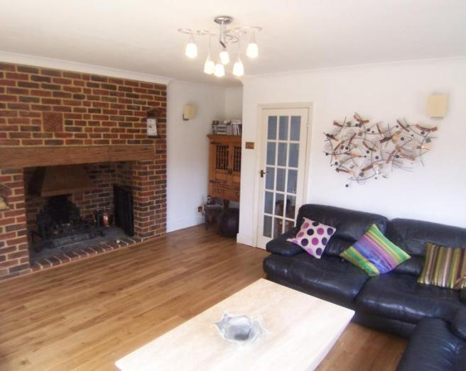 photo of beige brown white lounge with inglenook fireplace wooden floor wall art and leather sofa